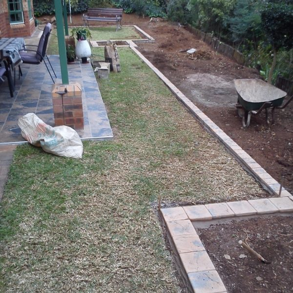 Formal-garden-3: Garden landscaped in Woodgrove retirement village, Pietermaritzburg with cobble edging, gravel garden feature and beds planted with pink Gaura.