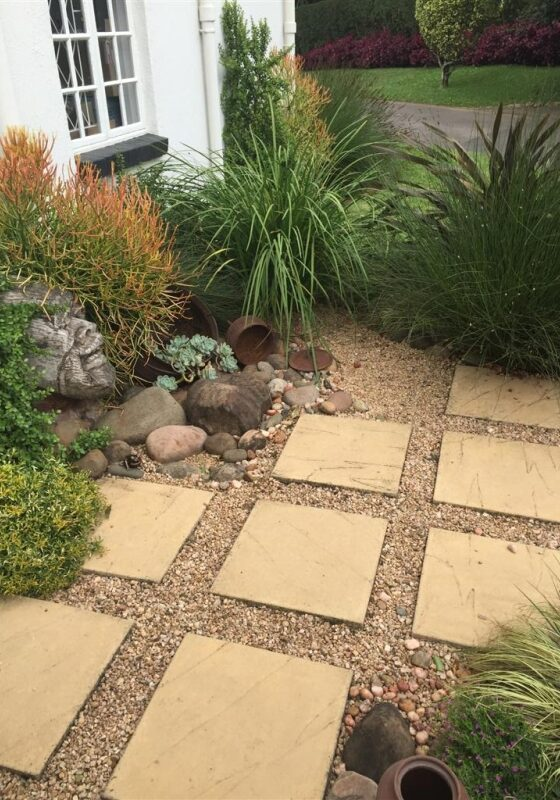 African-garden-2: An entrance garden using spaced paving inset with river gravel and planted with a mixed form and textured plants in Hillcrest, KZN.